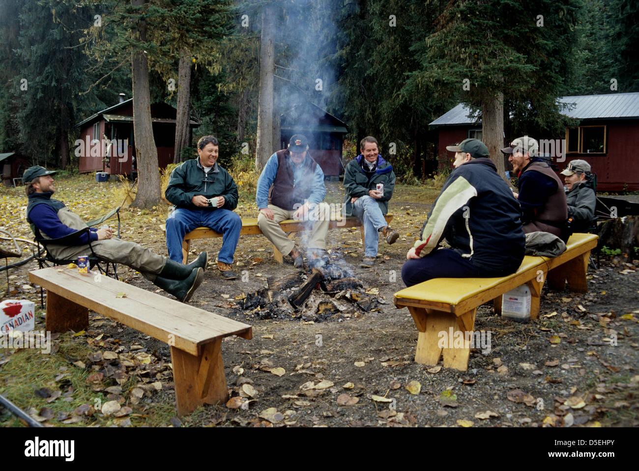 steelhead fly fishermen sitting around a campfire at a fishing lodge