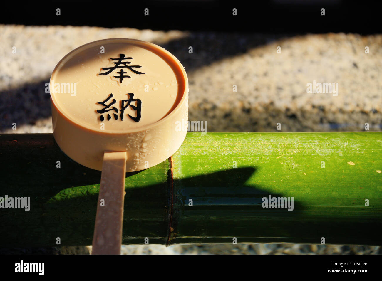 Scoop set atop a ritualistic tsukubai hand-washing basin with Japanese Kanji charachters reading 'dedication.' - Stock Image