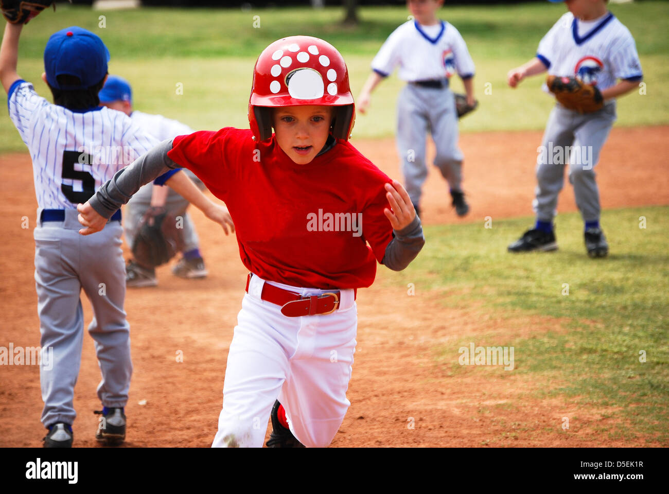 Youth little league baseball boy running bases. - Stock Image