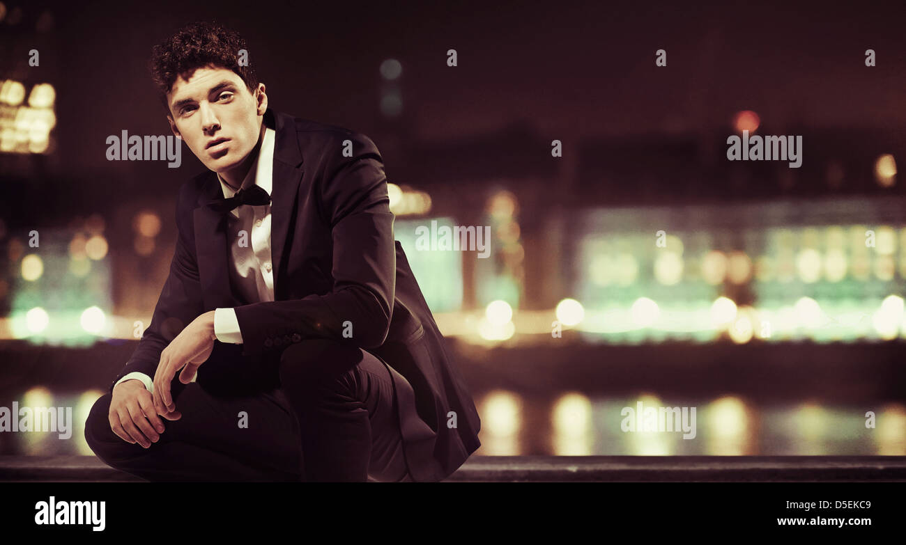 Stylish young man with night town over the background Stock Photo
