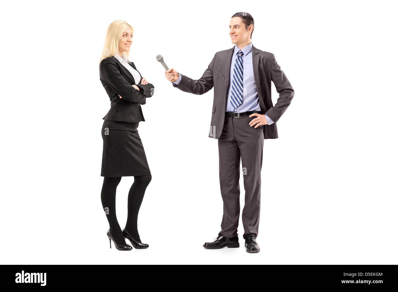 Full length portrait of a businesswoman and male reporter having an interview, isolated on white background - Stock Image