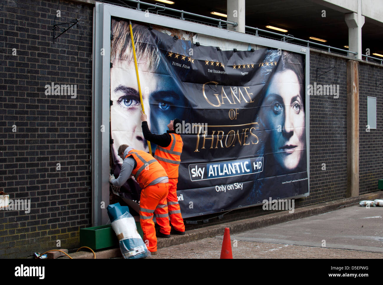 Men putting up billboard poster, Coventry railway station, UK - Stock Image