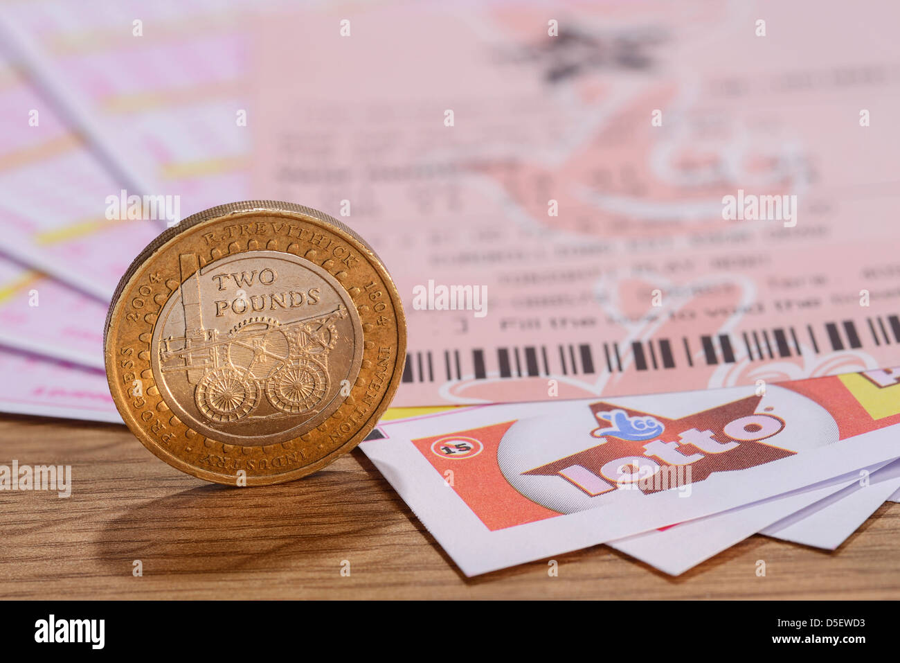 UK Lotto tickets with a two pound coin - Stock Image