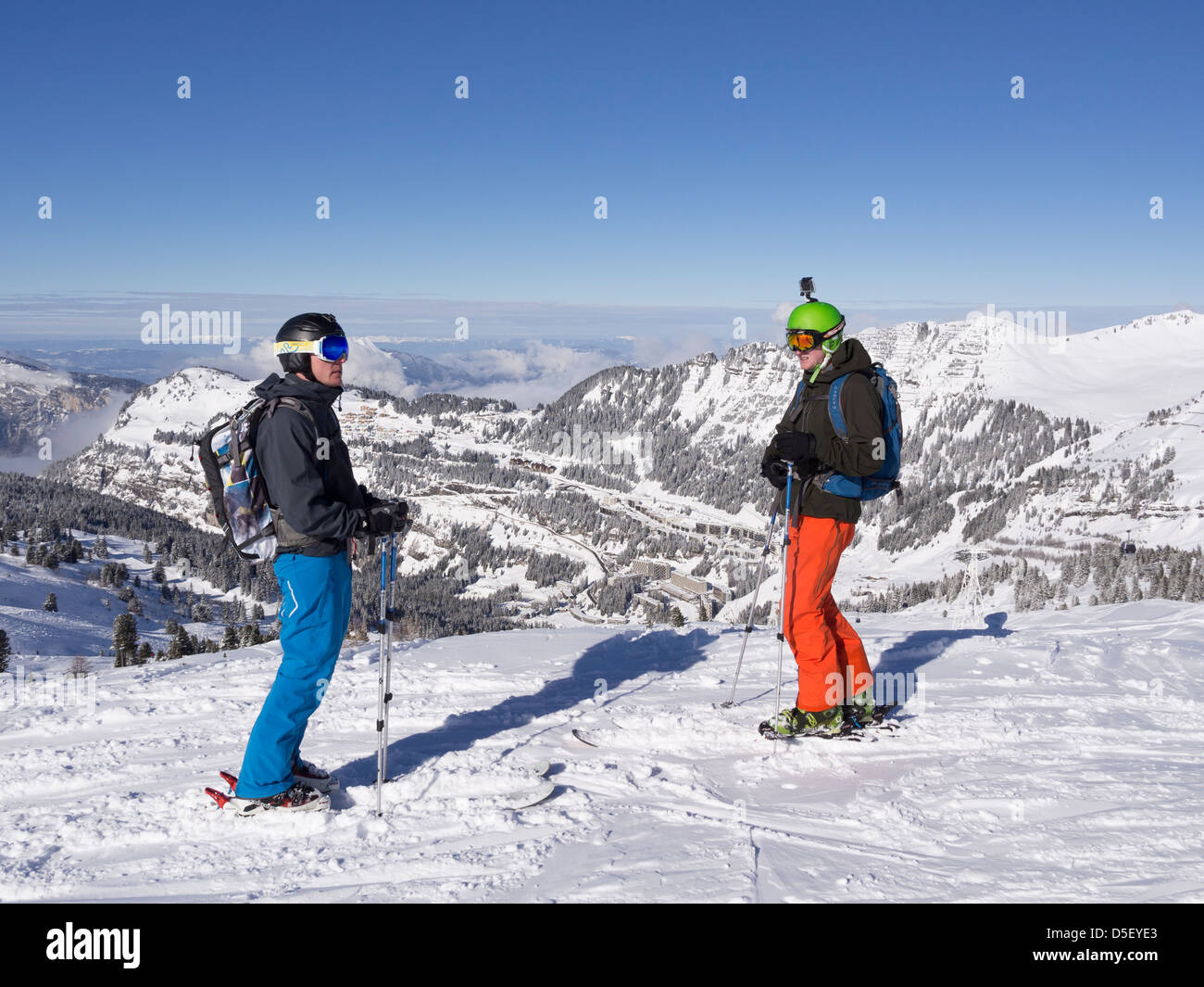 Two skiers skiing on blue snow slope Traversee Damant Noir in Le Grand Massif ski area in French Alps above Flaine - Stock Image