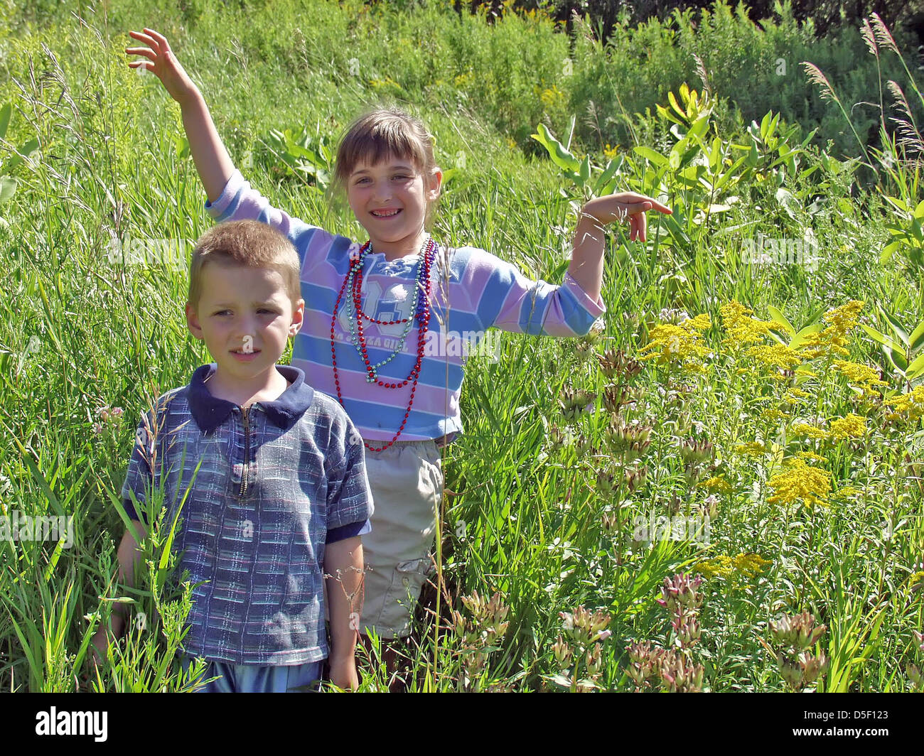 Two Children; a 4 year old Boy and a 6 year old girl, are playing in a field of yellow flowers near their farm in Stock Photo