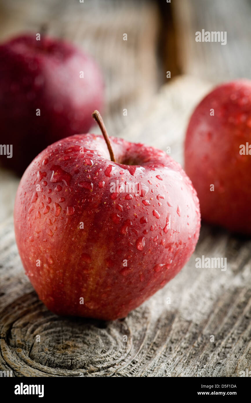 Three red apples on wooden table, selective focus - Stock Image