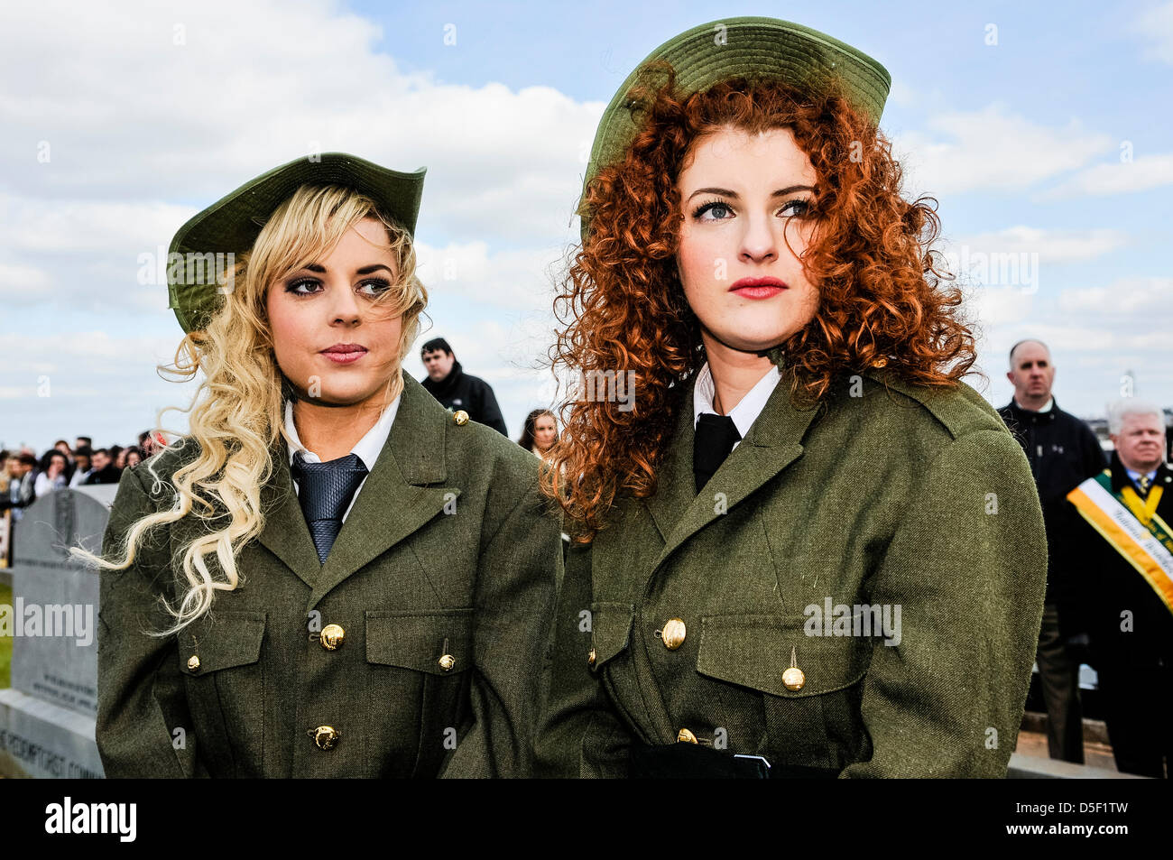 Two pretty girls wearing old fashioned soldier uniforms while listening to a speech to commemorate the anniversary - Stock Image