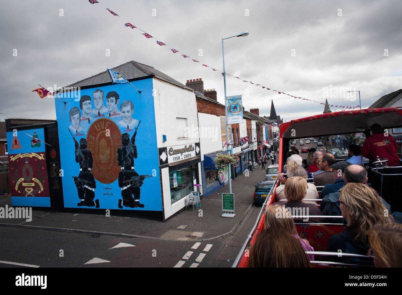 A tourist bus travels along the Shankill Road, Belfast, Northern Ireland. - Stock Image