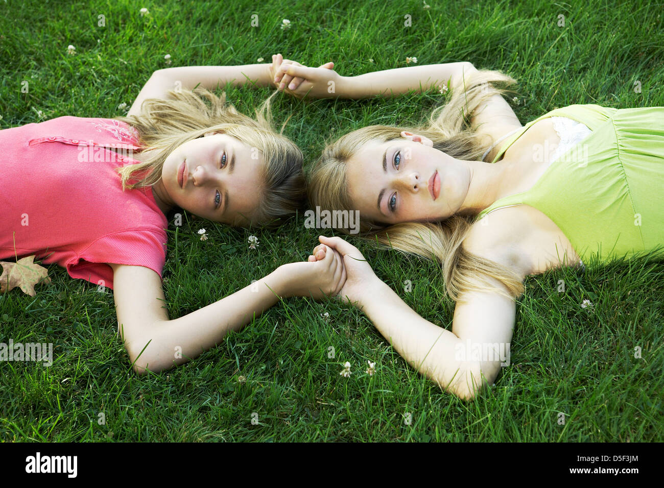 Beautiful teen and tween sisters holding hands - Stock Image