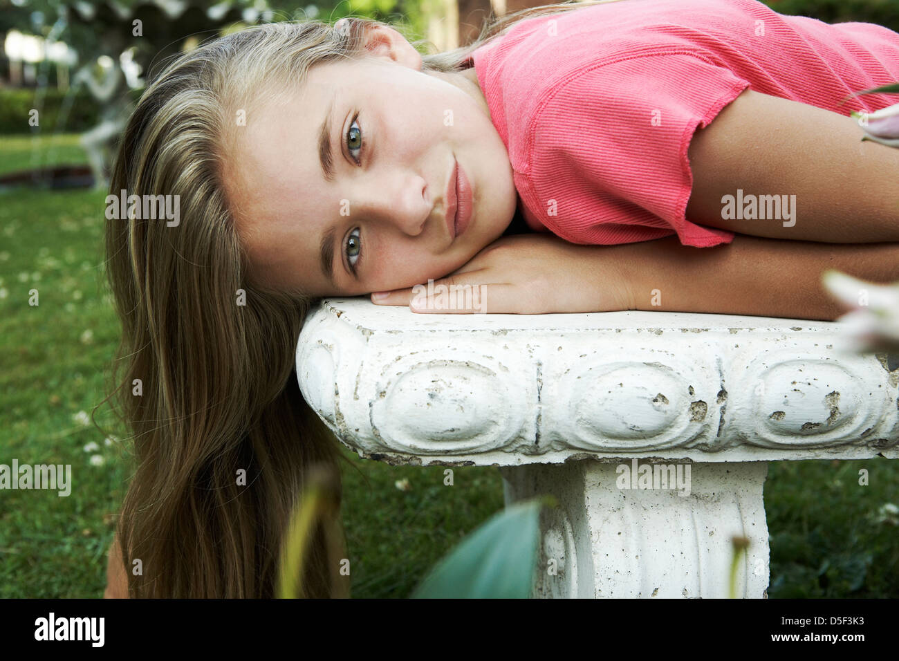 Beautiful tween lying on garden bench - Stock Image