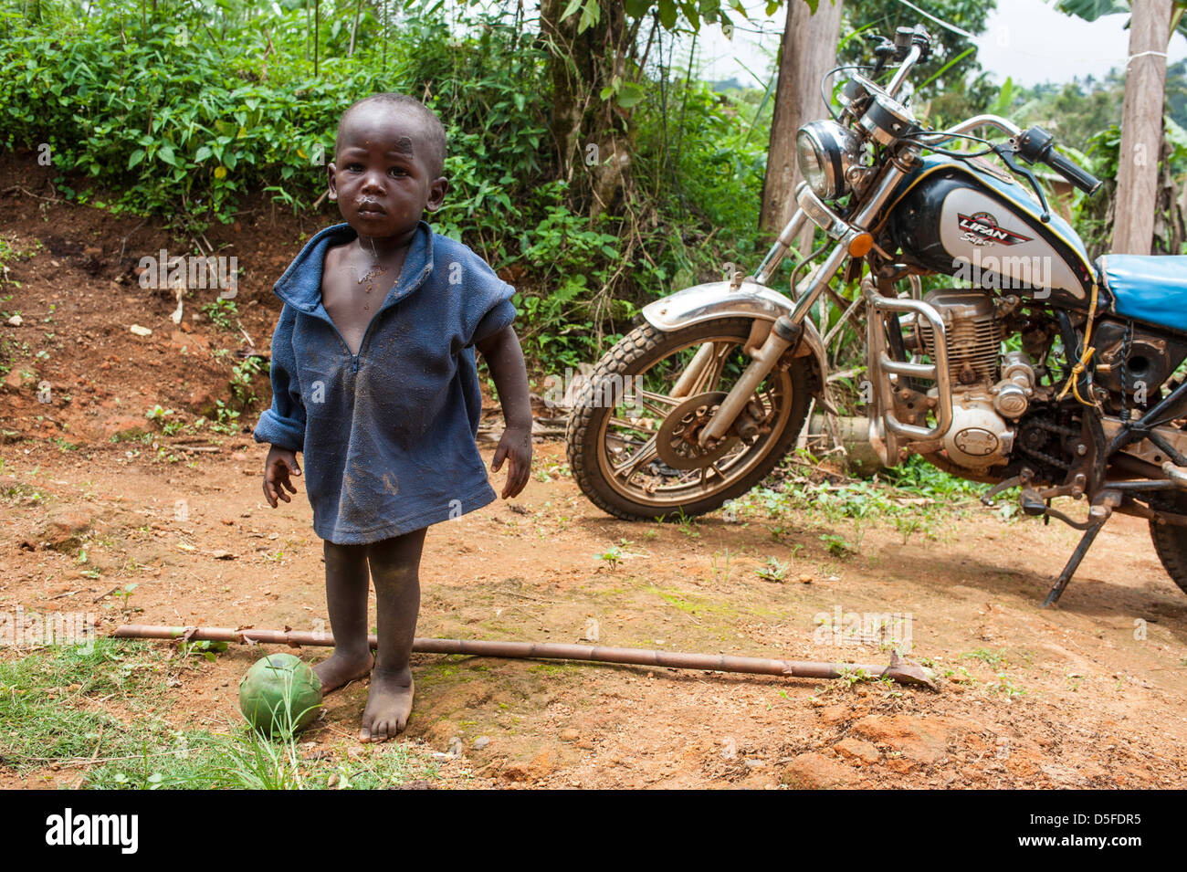 Young African boy with cabbage at his feet with motorcycle in background in Cameroon Africa - Stock Image