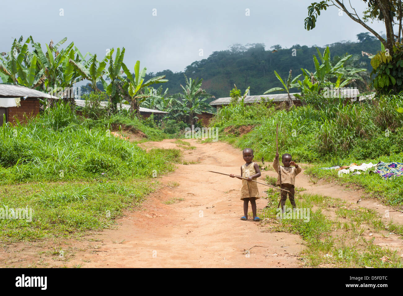 Two african children in rags on a dirt road outside of a village in Cameroon Africa - Stock Image