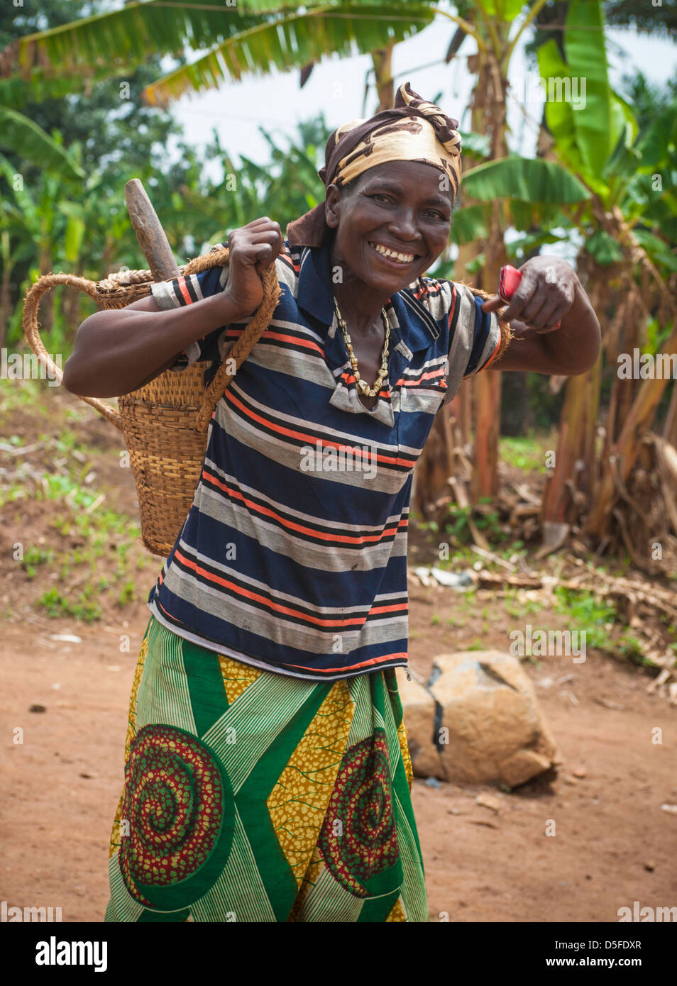 African woman carrying basket as she goes to the field in Cameroon to work - Stock Image