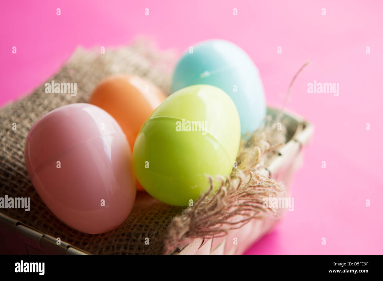 A Basket Of Coloured Plastic Easter Eggs Against Bright Pink Background