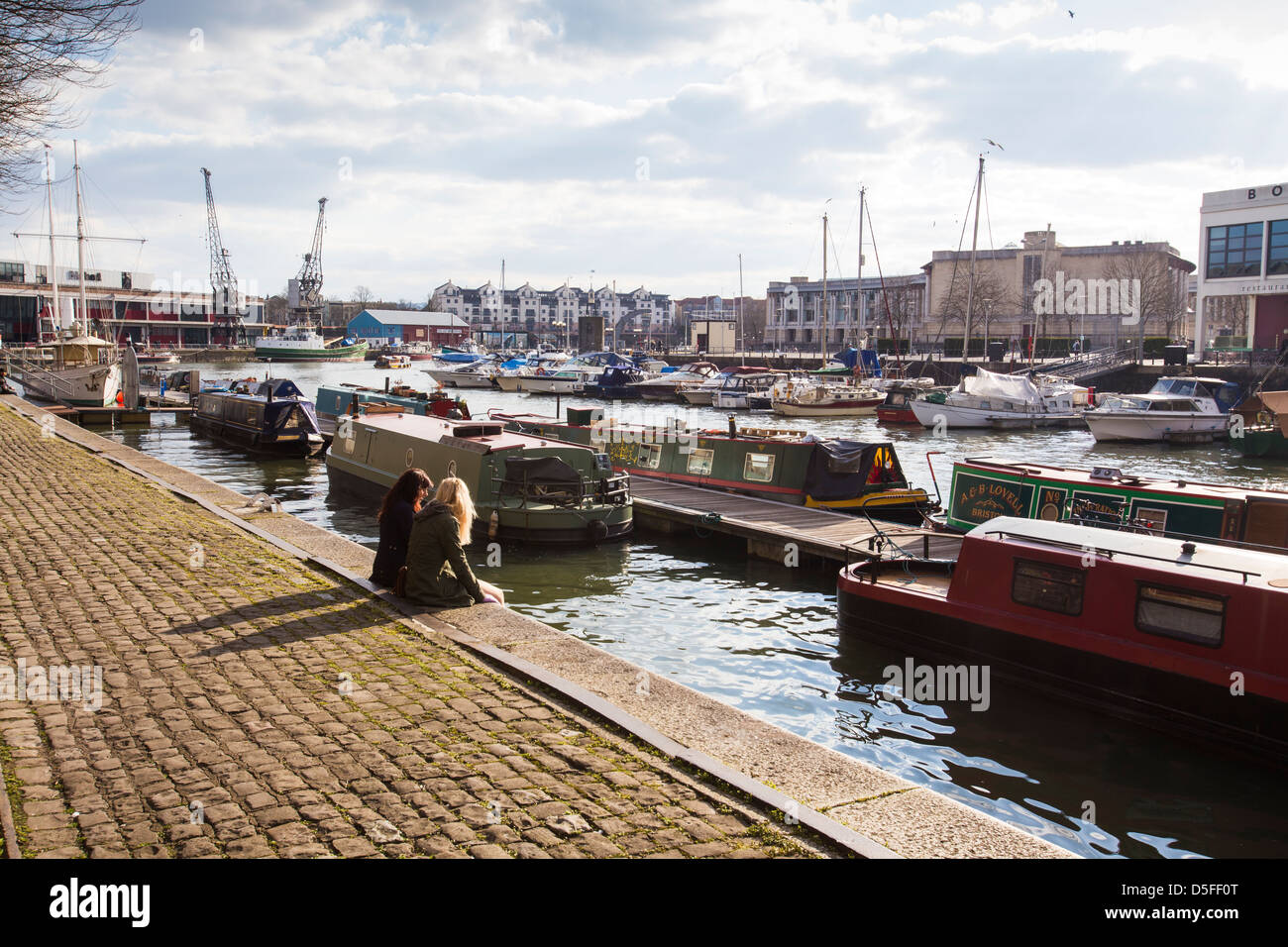 Two girls sitting at the water's edge on Narrow Quay in Bristol Harbour in Bristol, UK - Stock Image