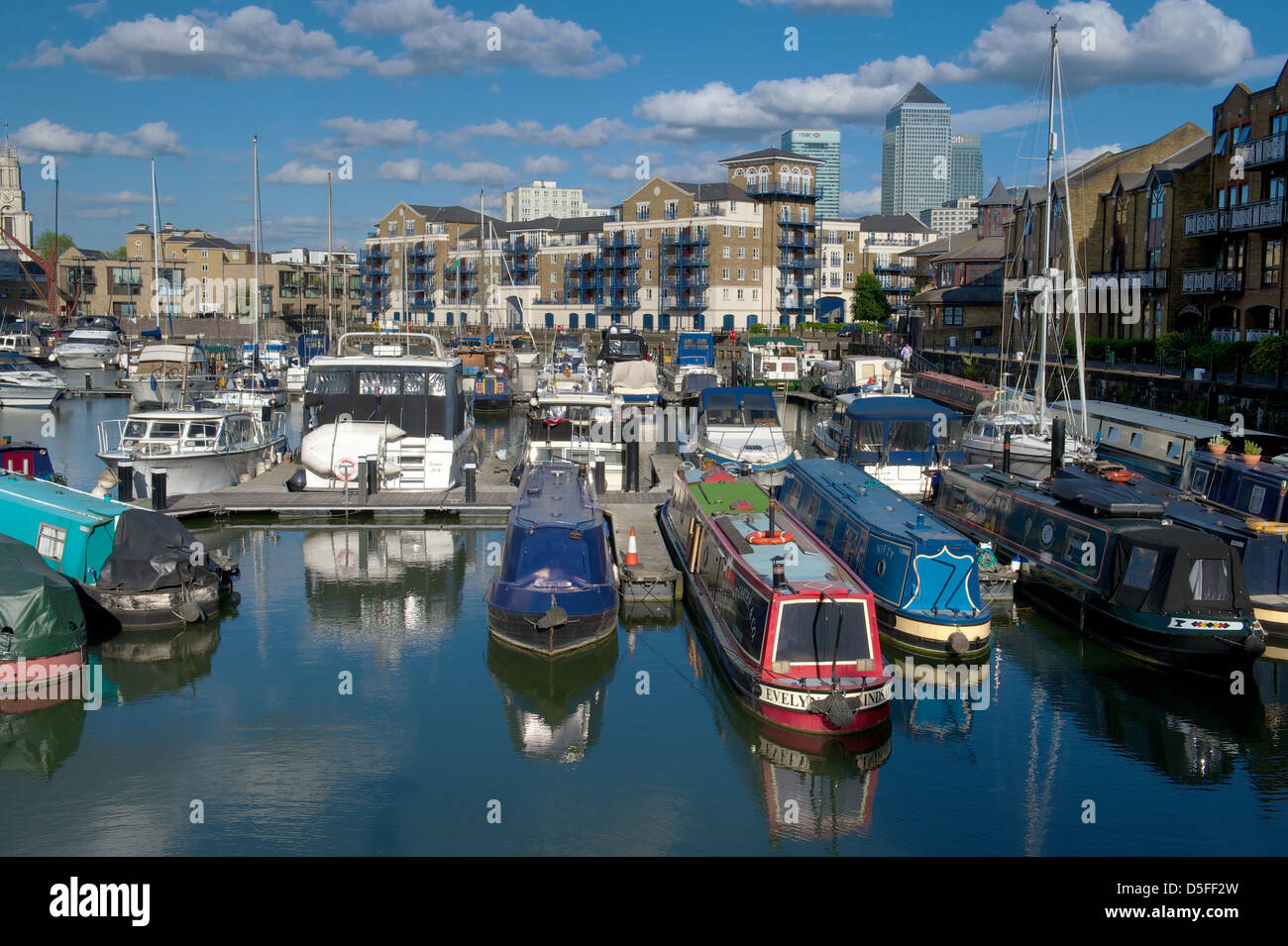 Narrow boats moored in Limehouse Basin with residential apartments and Canary Wharf in the background, London, UK - Stock Image