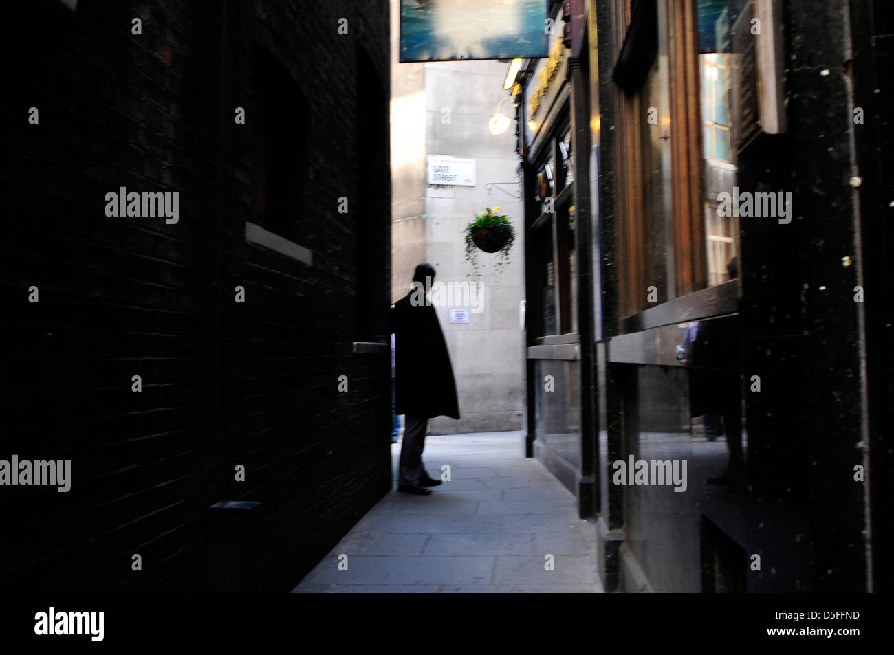 A man waits in an alleyway, Holborn, London, UK. - Stock Image