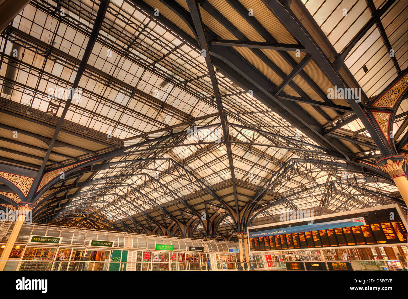 Intricate cast iron glazed Victorian engineering and detail of roof at Liverpool street station with concourse beneath - Stock Image