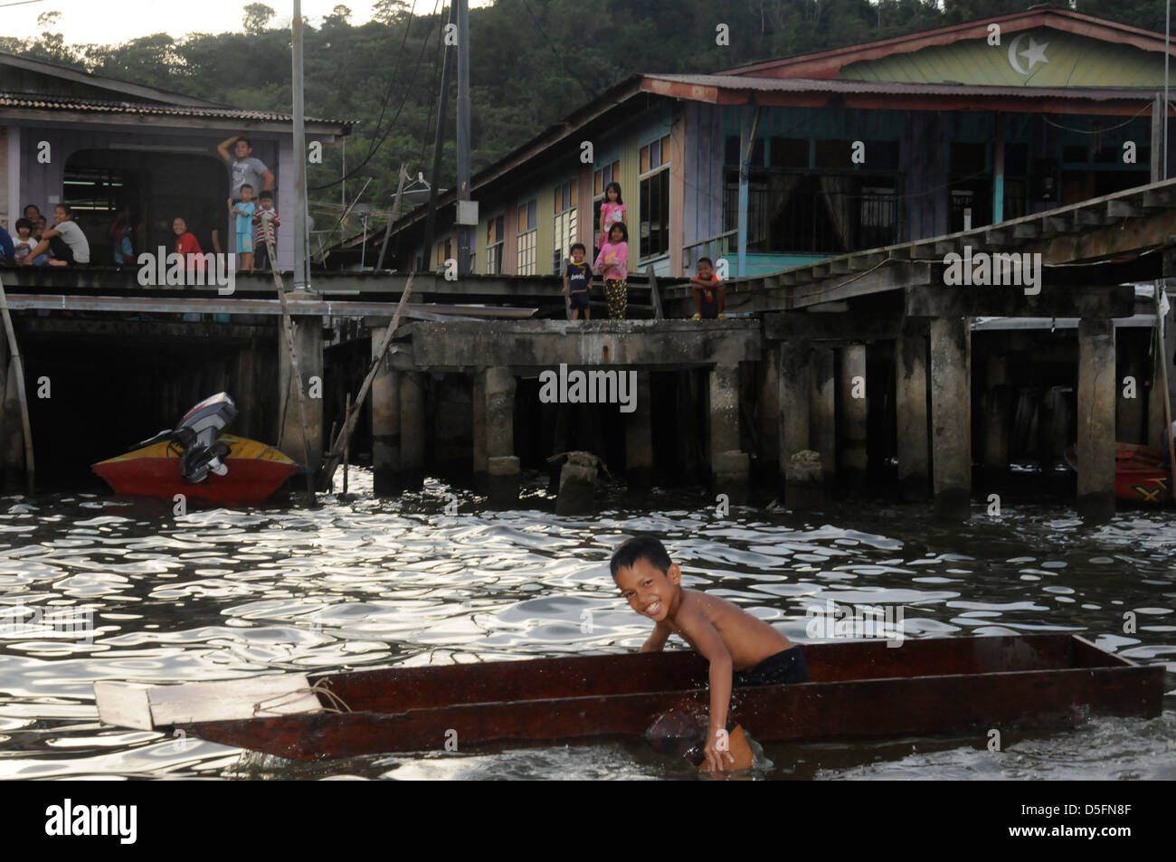 Boy paddling in front of Kampong Ayer - the worlds largest Water Village - Stock Image