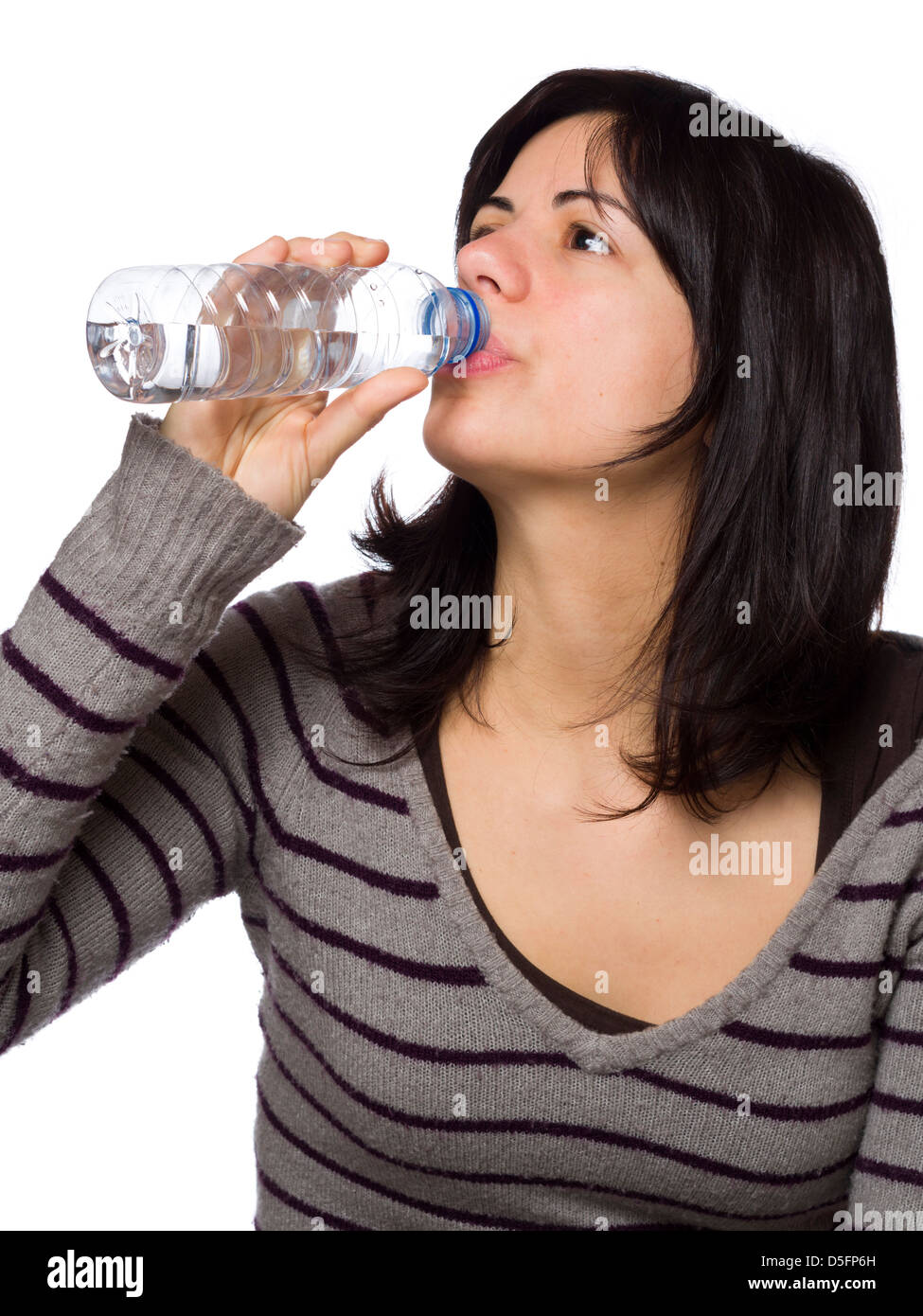 Young woman drinking water from plastic bottle on white background - Stock Image