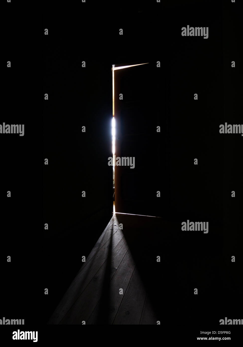 Door ajar at the end of a dark corridor letting some light trough in a menacing and scary way - Stock Image