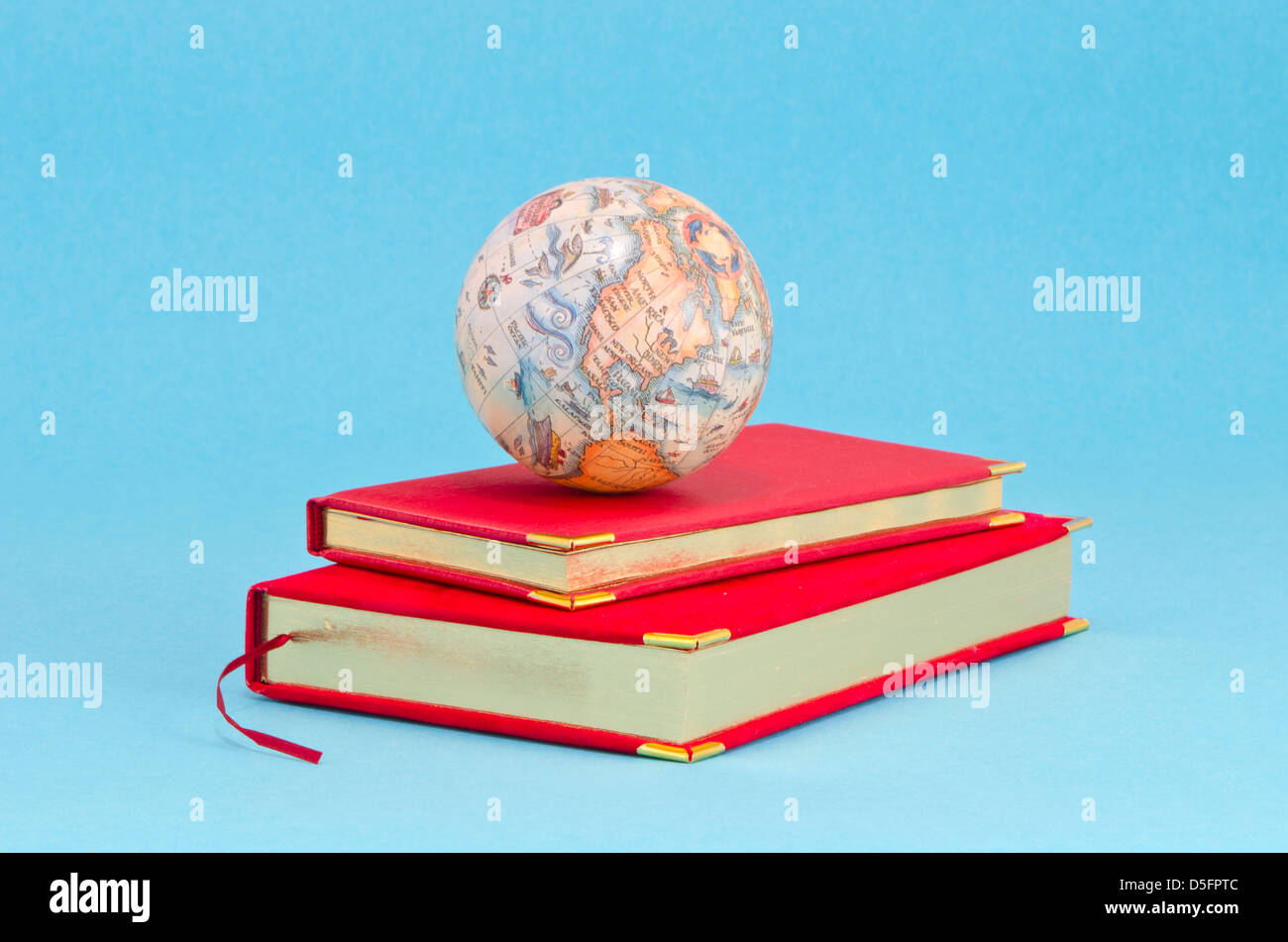 gilded business diary with small earth globe on azure background - Stock Image