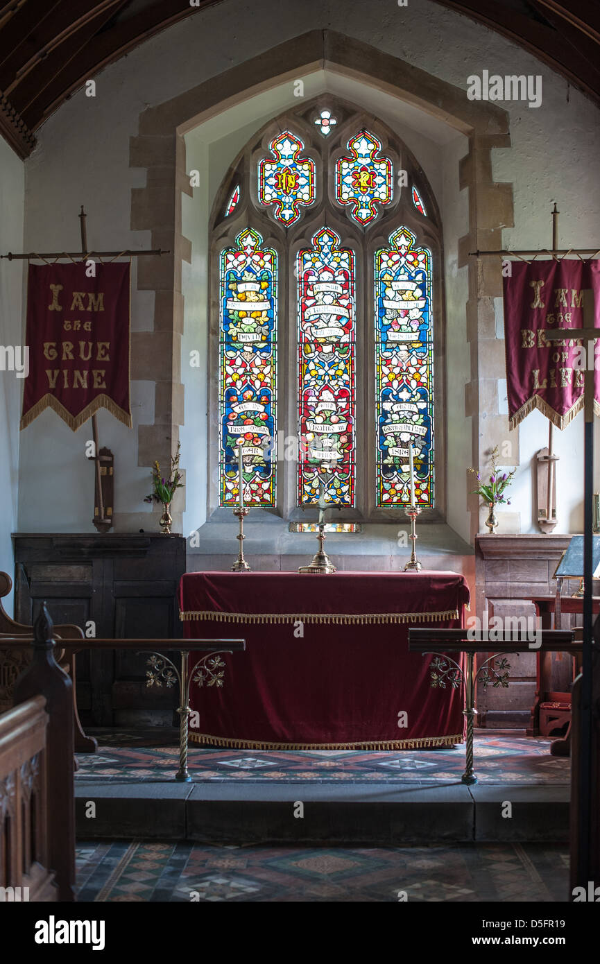 Church altar with morning light through the stained glass window in the historic country church St Mary De Malmsbury, Stock Photo