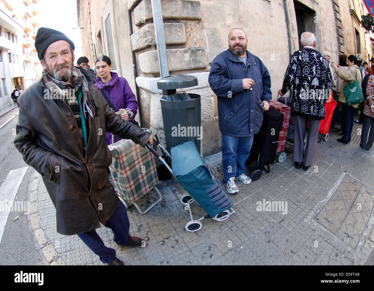 Unemployed or low resources people wait at the door of a charity center for a bag of goods. - Stock Image