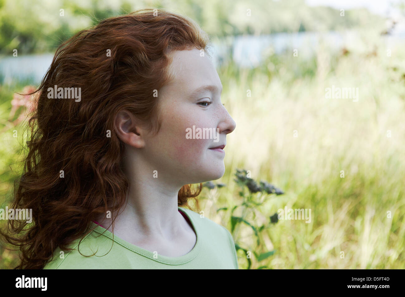 Red head girl in profile. - Stock Image