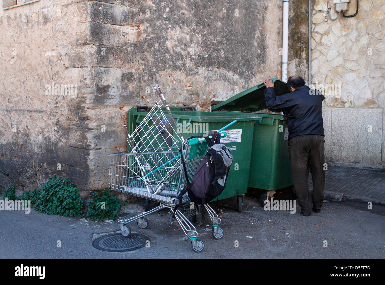 A jobless man pulls a trolley to carry the junk found on the bins. - Stock Image