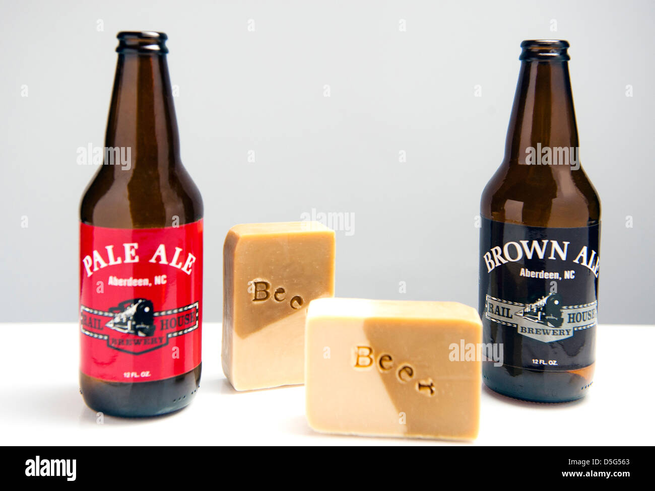 Bars of soap made with beer arranged in a still life with the bottles of ale they were made from - Stock Image