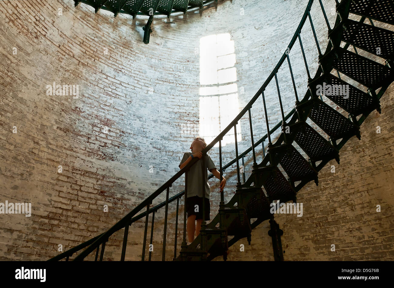 Boy marvels at the interior of a lighthouse, Corolla Lighthouse, Outer Banks, NC, North Carolina - Stock Image