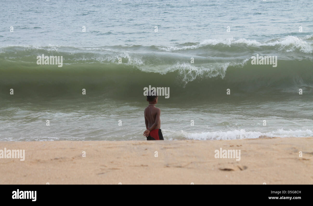 An Indian child standing alone watching the sea waves - Stock Image