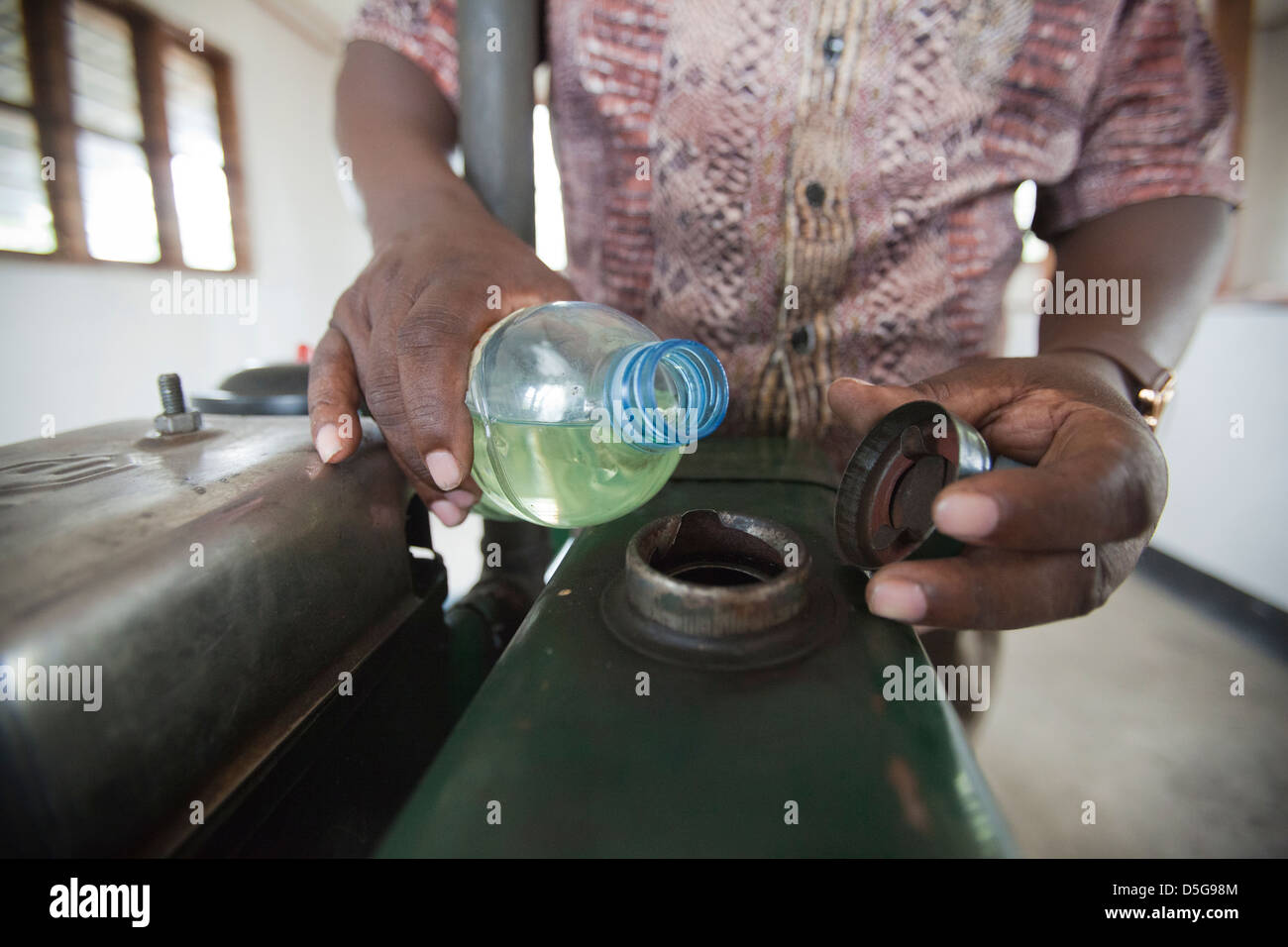 Man pouring Jatropha biofuel from a bottle to fuel a milling machine, Tanzania. - Stock Image