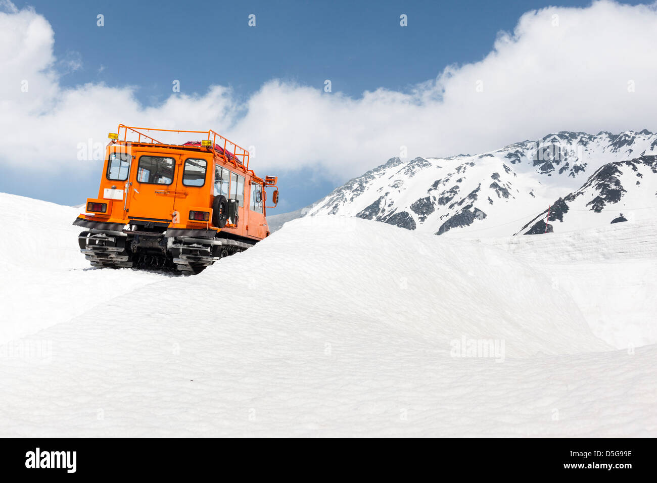 Back view of a mountain rescue vehicle with caterpillar tracks on a snow-capped mountain - Stock Image