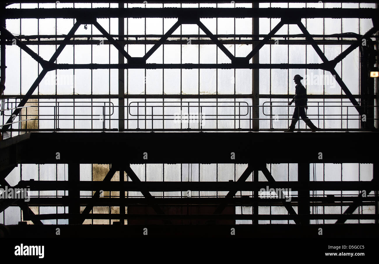 A workman walks across a gantry in a power station. - Stock Image