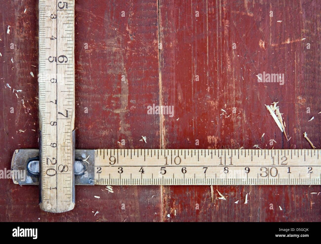 Old wooden meter stick on vintage red wooden background - DIY concept - Stock Image