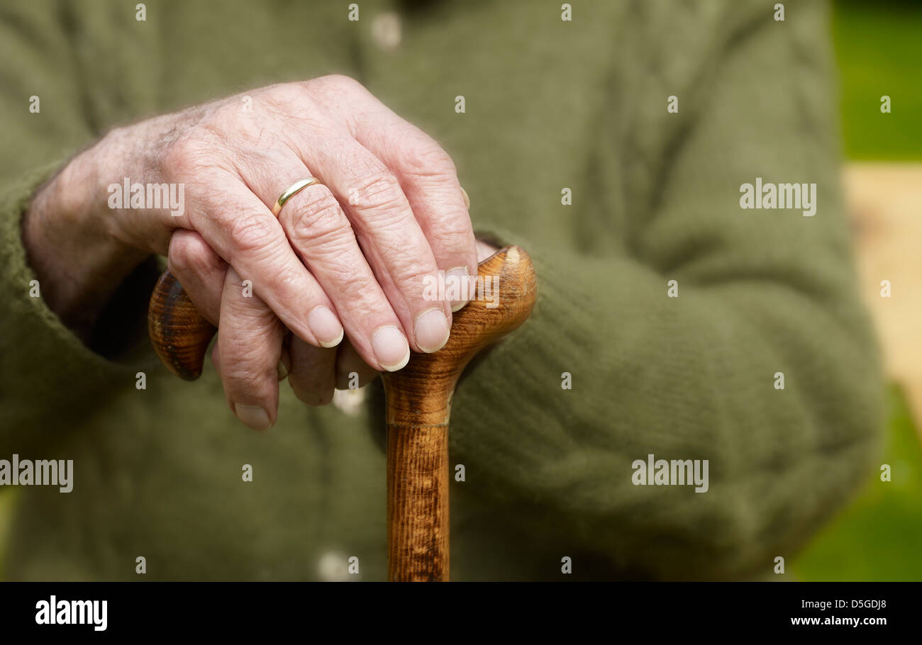 old hands of a senior on walking stick - Stock Image