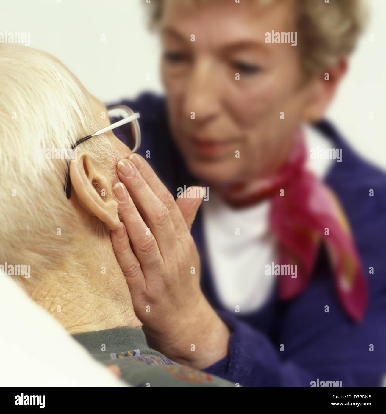 Frau taetschelt pflegebeduerftigen alten Mann die Wange |woman chucks an old man dependent on care| - Stock Image
