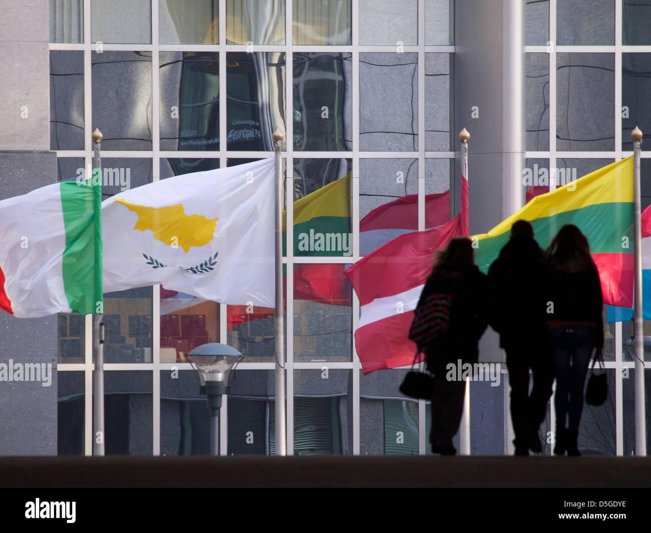 Various EU member state flags in Brussels, Belgium with silhouetted group of people walking - Stock Image