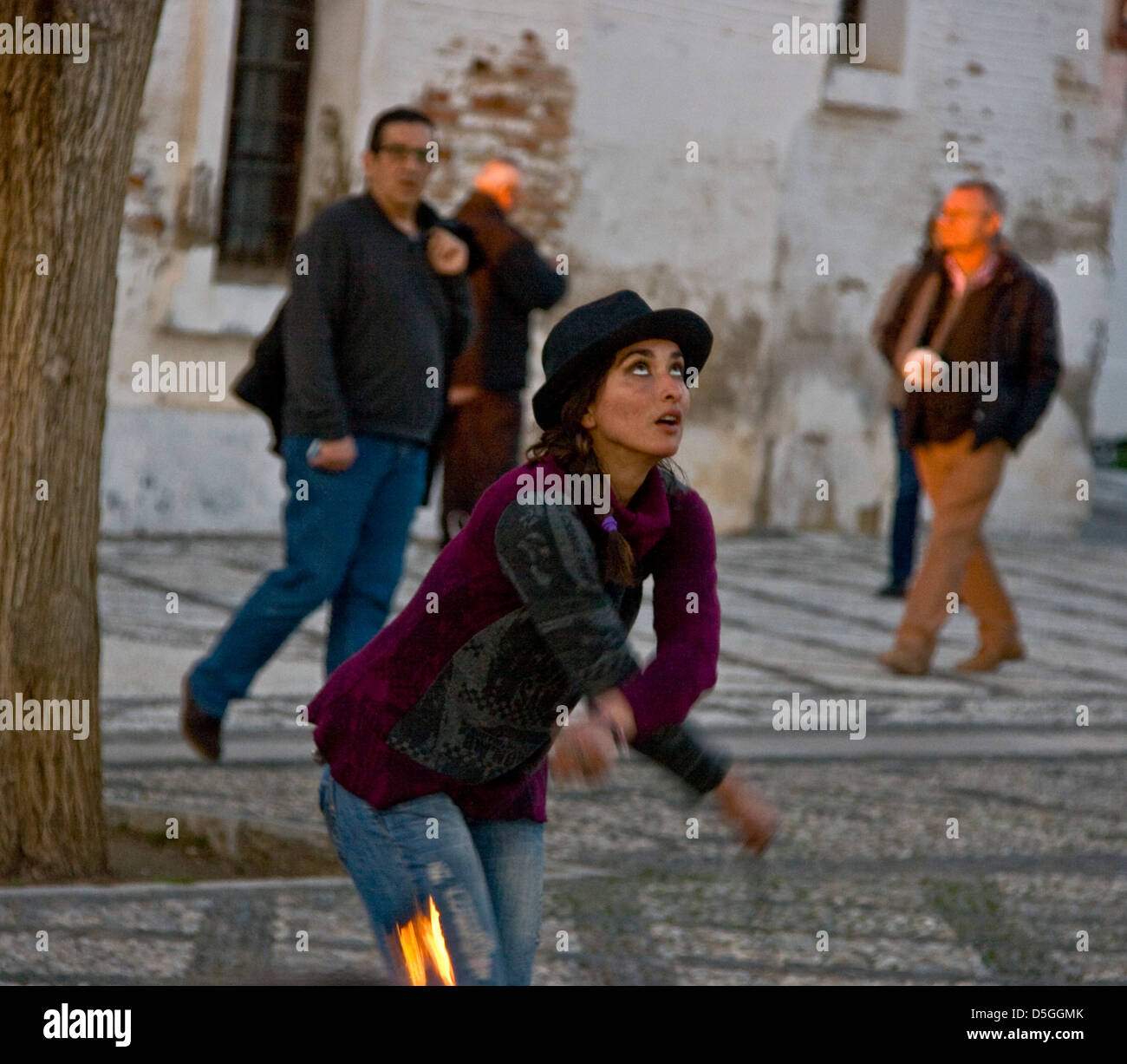 Female fire eating juggler performing at dusk Mirador San Nicolas Granada Andalusia Spain Europe - Stock Image