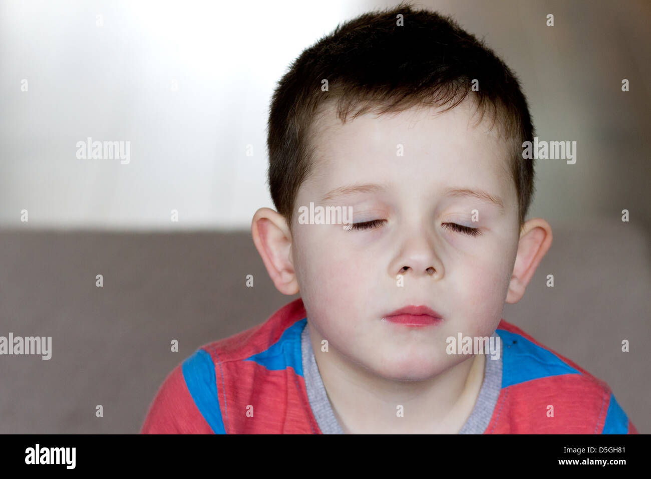 little boy with his eyes tight shut - Stock Image