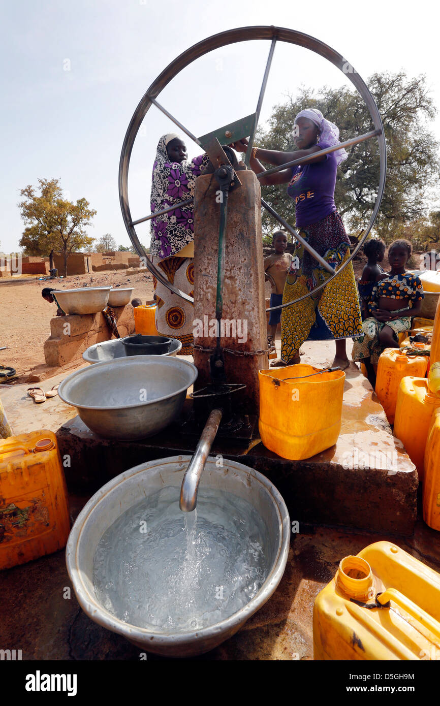 Women turn the wheel of a water pump in a village, Burkina Faso, Africa - Stock Image