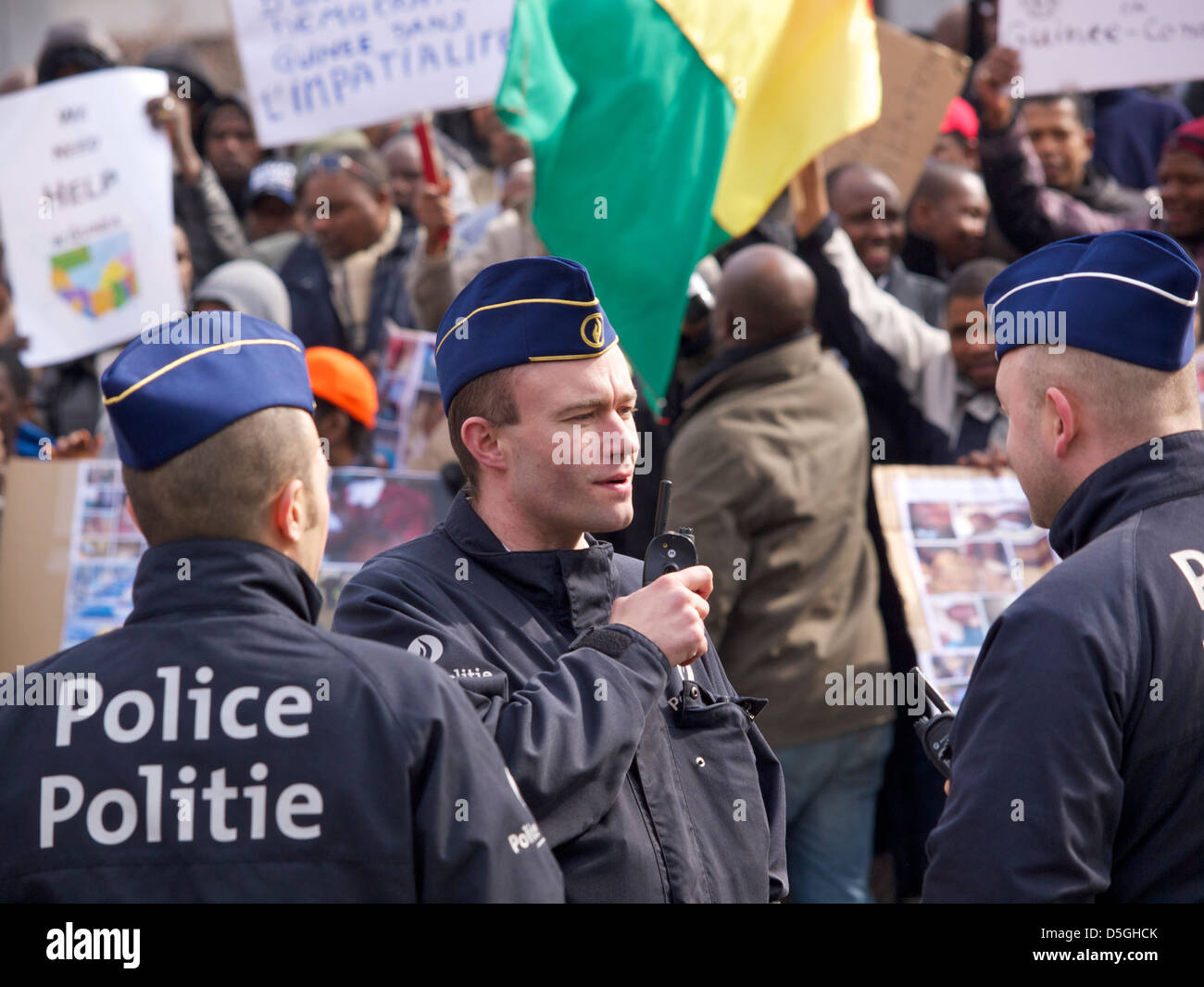Policemen talking to each other at protest against dictator Alpha Conde of Guinea. Brussels, Belgium - Stock Image
