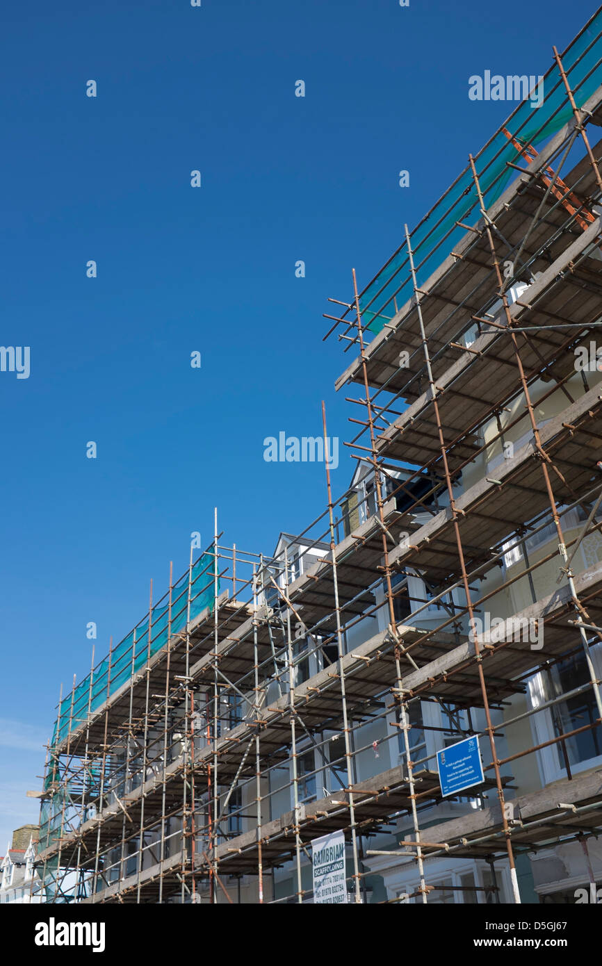 Houses covered in scaffolding, being renovated as part of an urban renewal scheme, Aberystwyth Wales UK - Stock Image