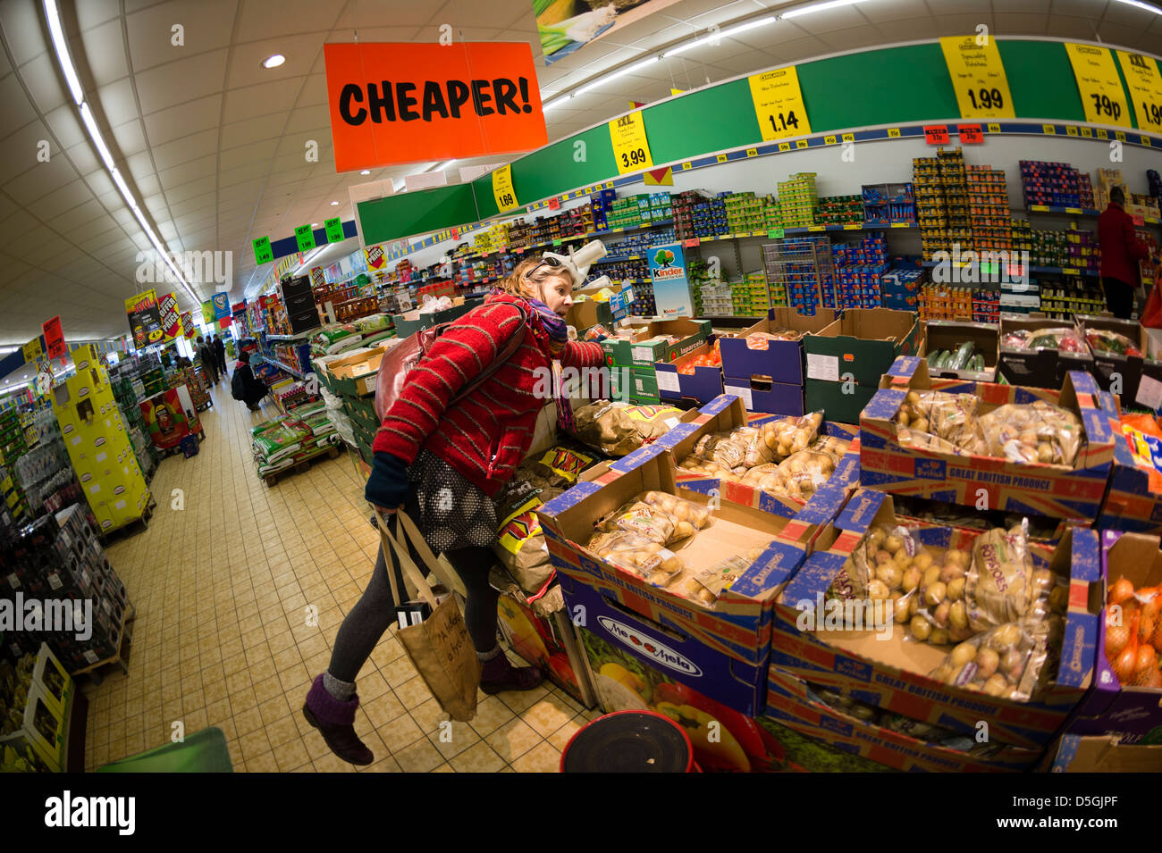 CHEAPER: A middle aged woman shopping for discount cheap affordable fresh vegetables in LIDL discount supermarket, - Stock Image
