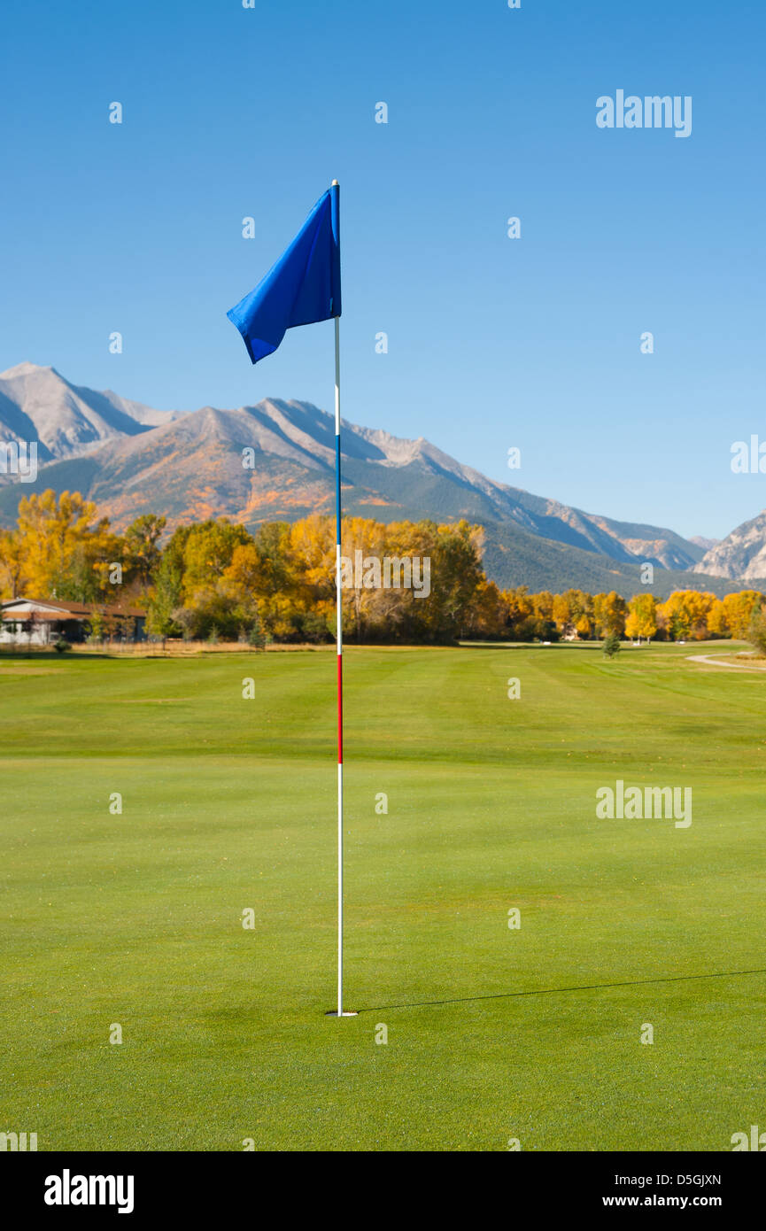 A scenic putting green on a golf course in the mountains of Colorado showcases the Fall season. - Stock Image