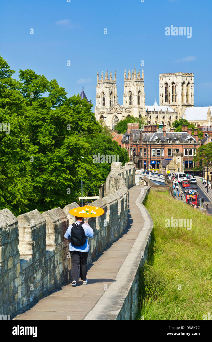 York Minster and tourist walking along a section of the historic city walls Station road York Yorkshire England - Stock Image