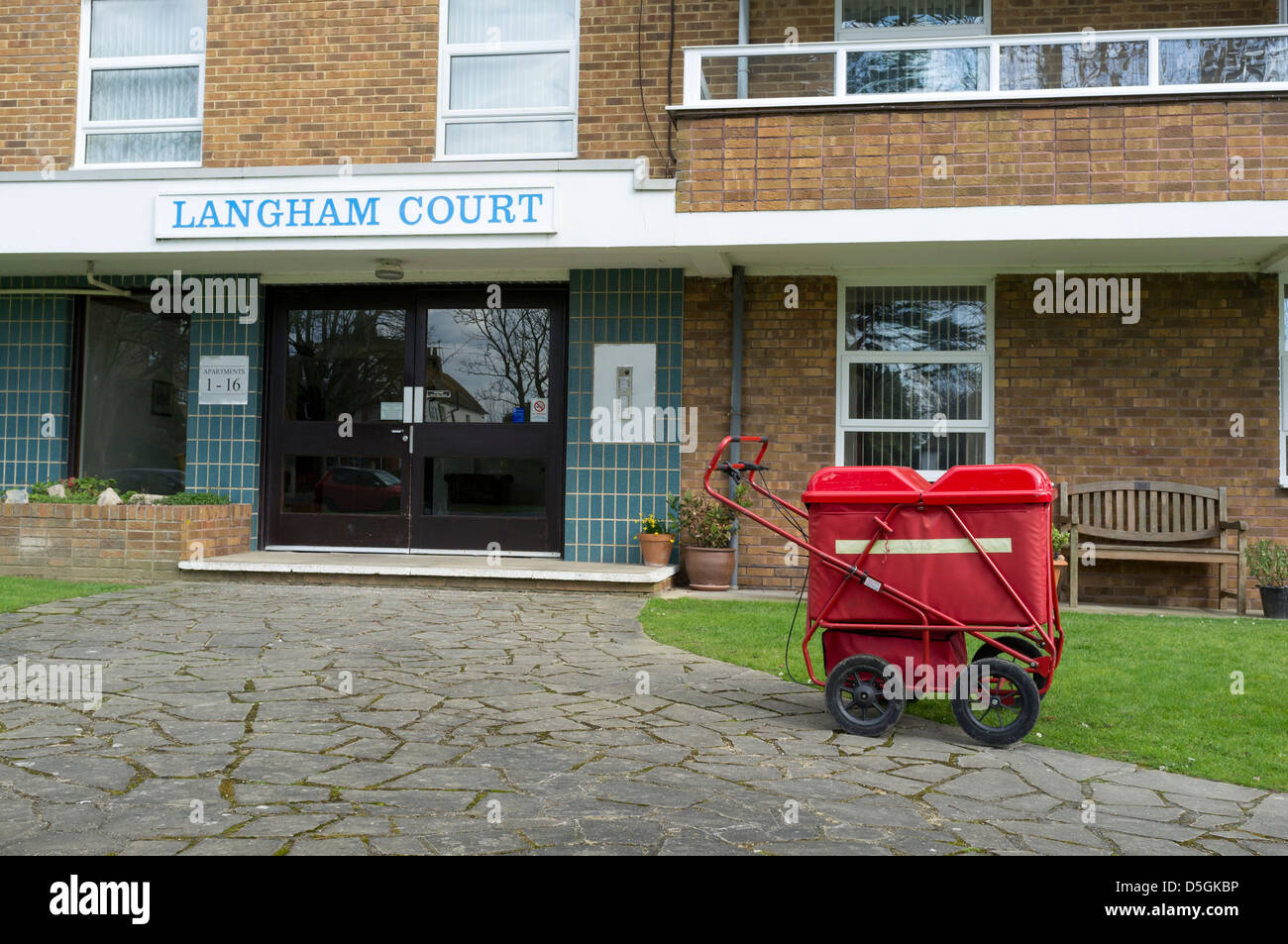 A british postman's trolley outside a block of flats whilst the postman delivers mail inside. Stock Photo