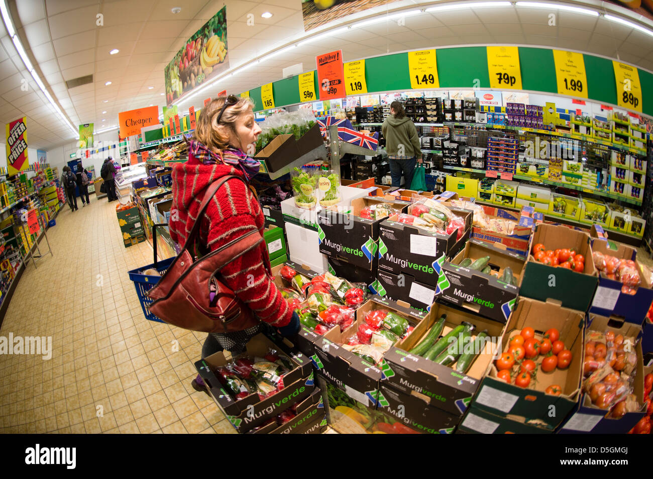 A middle aged woman shopping for fresh vegetables and other food in LIDL discount supermarket, UK - Stock Image